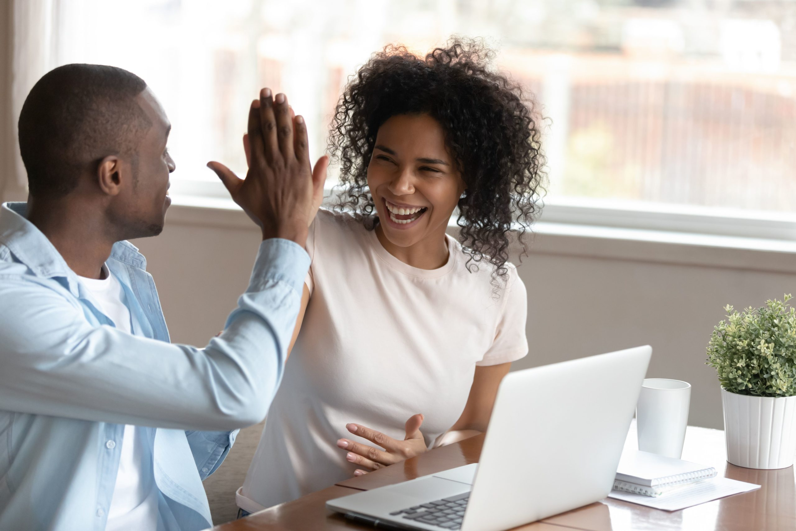 Two people high fiving at the desk